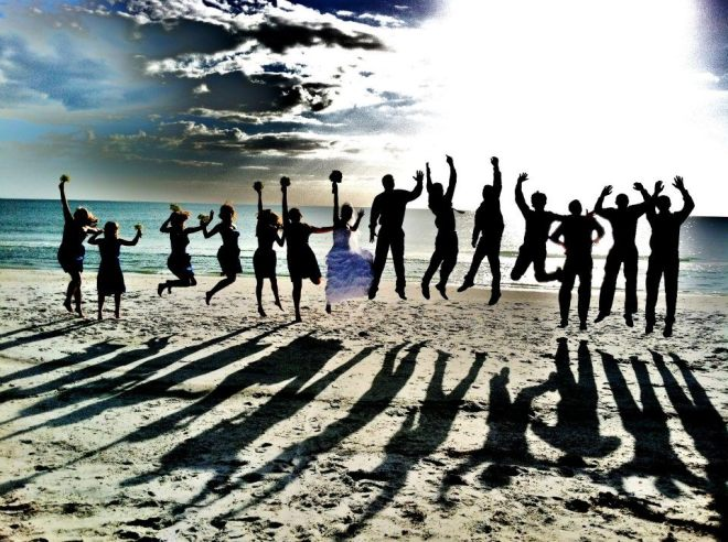 Beach photo jumping whole wedding party