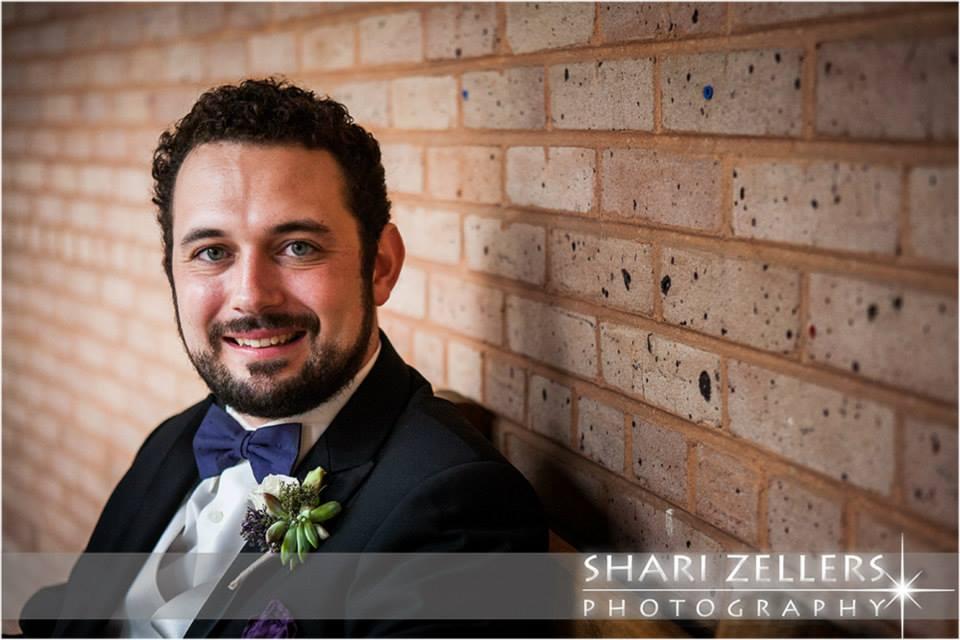 Groom at brickwall by Shari