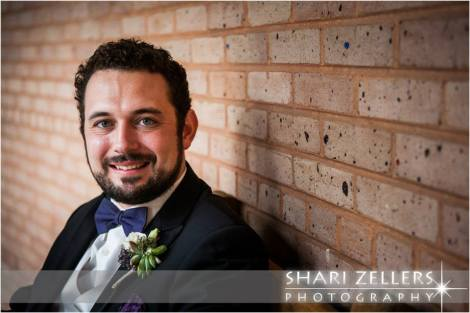 Groom at brickwall by Shari
