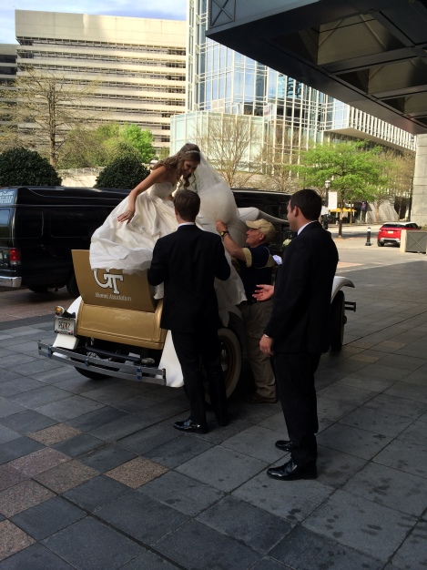 Groom helping Bride out of the GT Ramblin Wreck